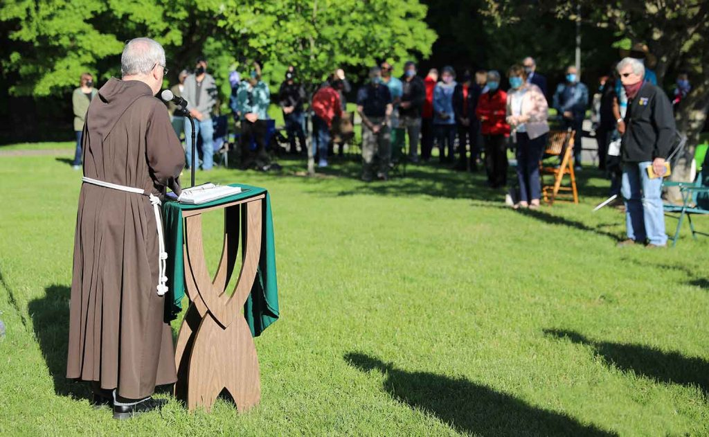 Fr. Tom Zelinski, Capuchin, addresses visitors on the front lawn of the retreat house.