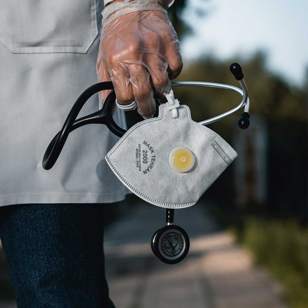 Health care worker holding stethoscope and N95 facemaks