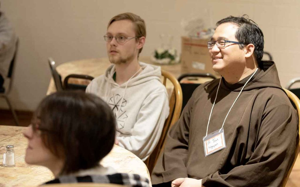 Fr. Tom Nguyen, OFM Cap. at a dining room table with young adults during a retreat