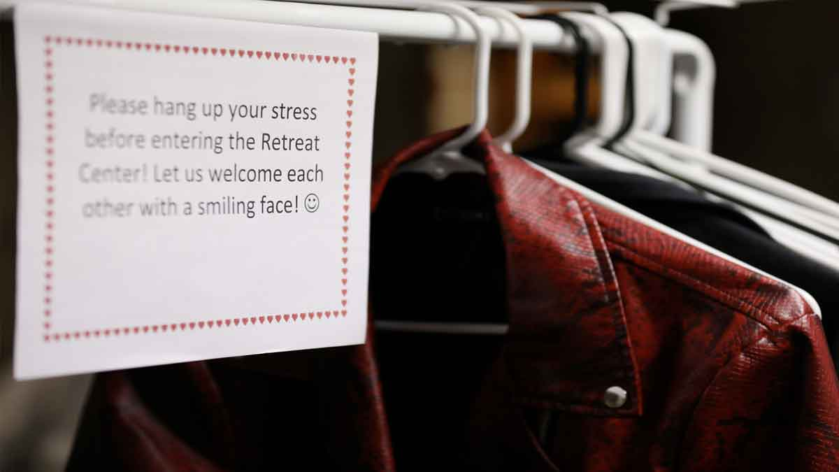 """Coat hanger with sign: """"Please hang up your stress before entering the Retreat Center. Let us welcome each other with a smiling face!"""