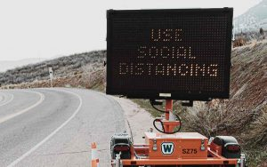 """Electronic road construction sign that reads """"Use Social Distancing"""""""