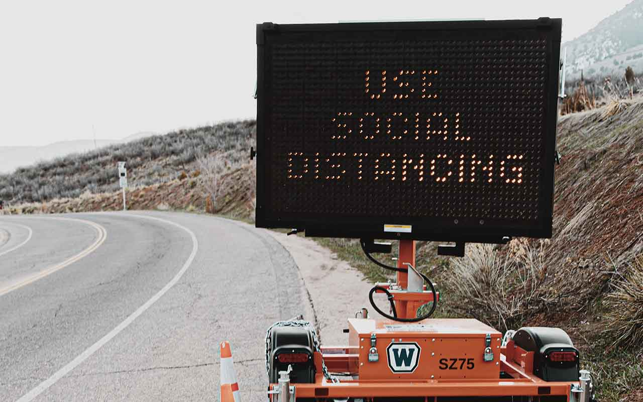 "Electronic road construction sign that reads ""Use Social Distancing"""